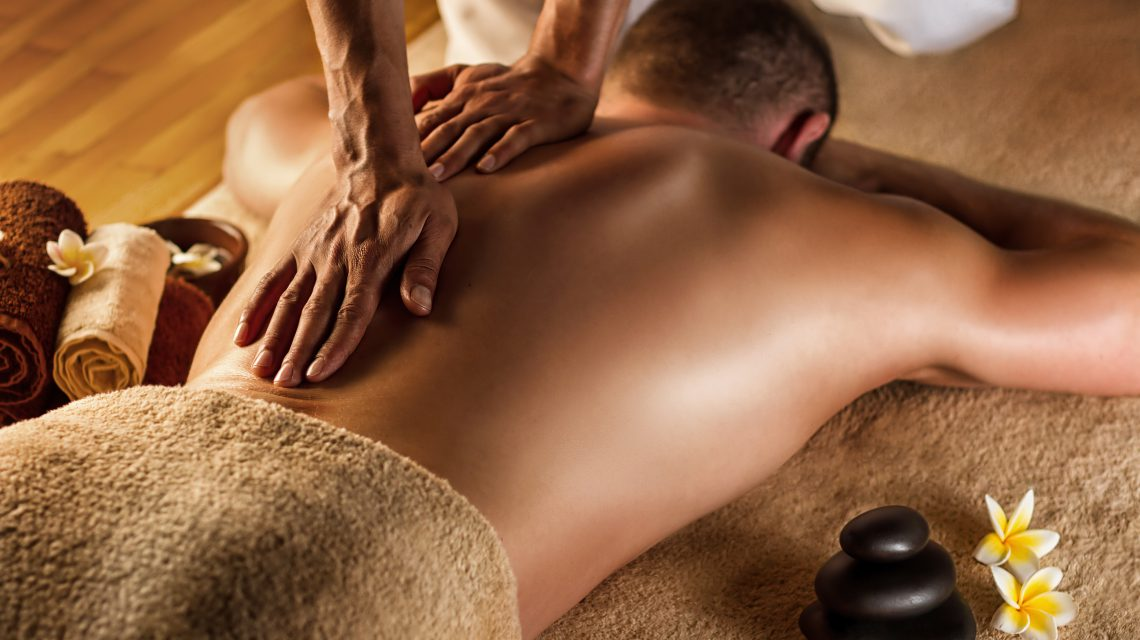 Man has deep tissue massage on the back. Spa stones and frangipani flowers. ** Note: Shallow depth of field