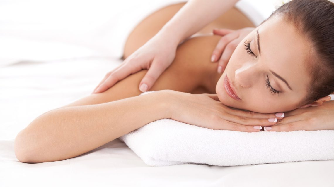 Beautiful young woman lying on front and looking at camera while massage therapist massaging her shoulders